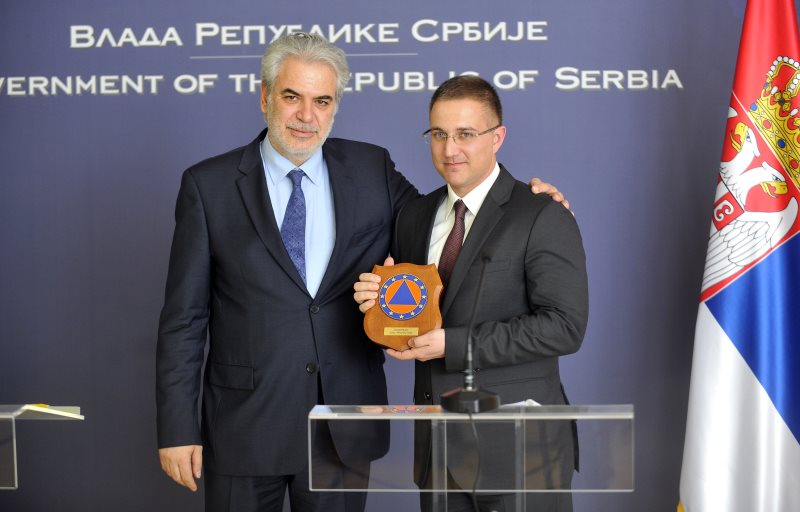 European Commissioner for Humanitarian Aid and Crisis Management Christos Stylianides gave him a plaque of EU Civil Protection  to  Serbia`s Internal Affairs Minister Nebojsa Stefanovic (right) signing of  Agreement on the participation of Serbia in the Union Civil Protection Mechanism   in Palace of Serbia , Belgrade on April, 16. 2015. AFP PHOTO / OLIVER BUNIC